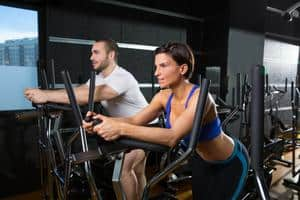 Man and woman standing on an elliptical