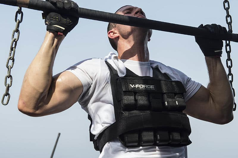 A man doing a pull-up while wearing a weighted vest