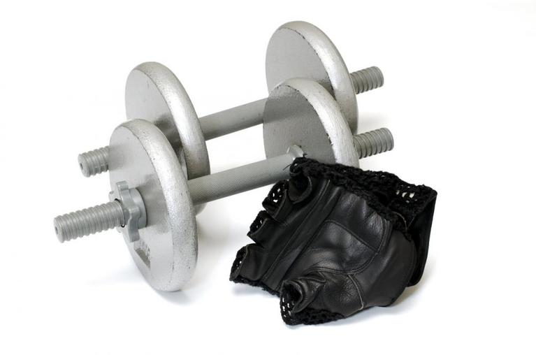 Isolated workout gloves and dumbbells